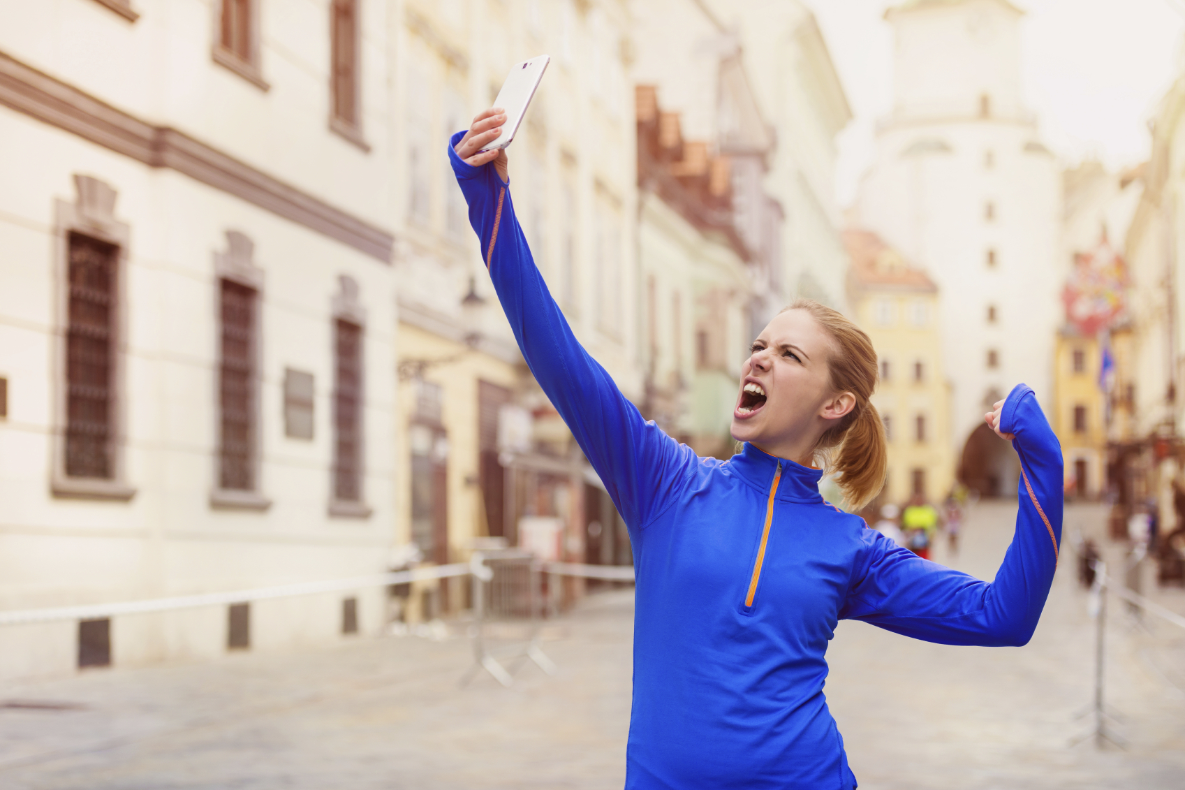 Beautiful young woman running in the city competition taking a selfie