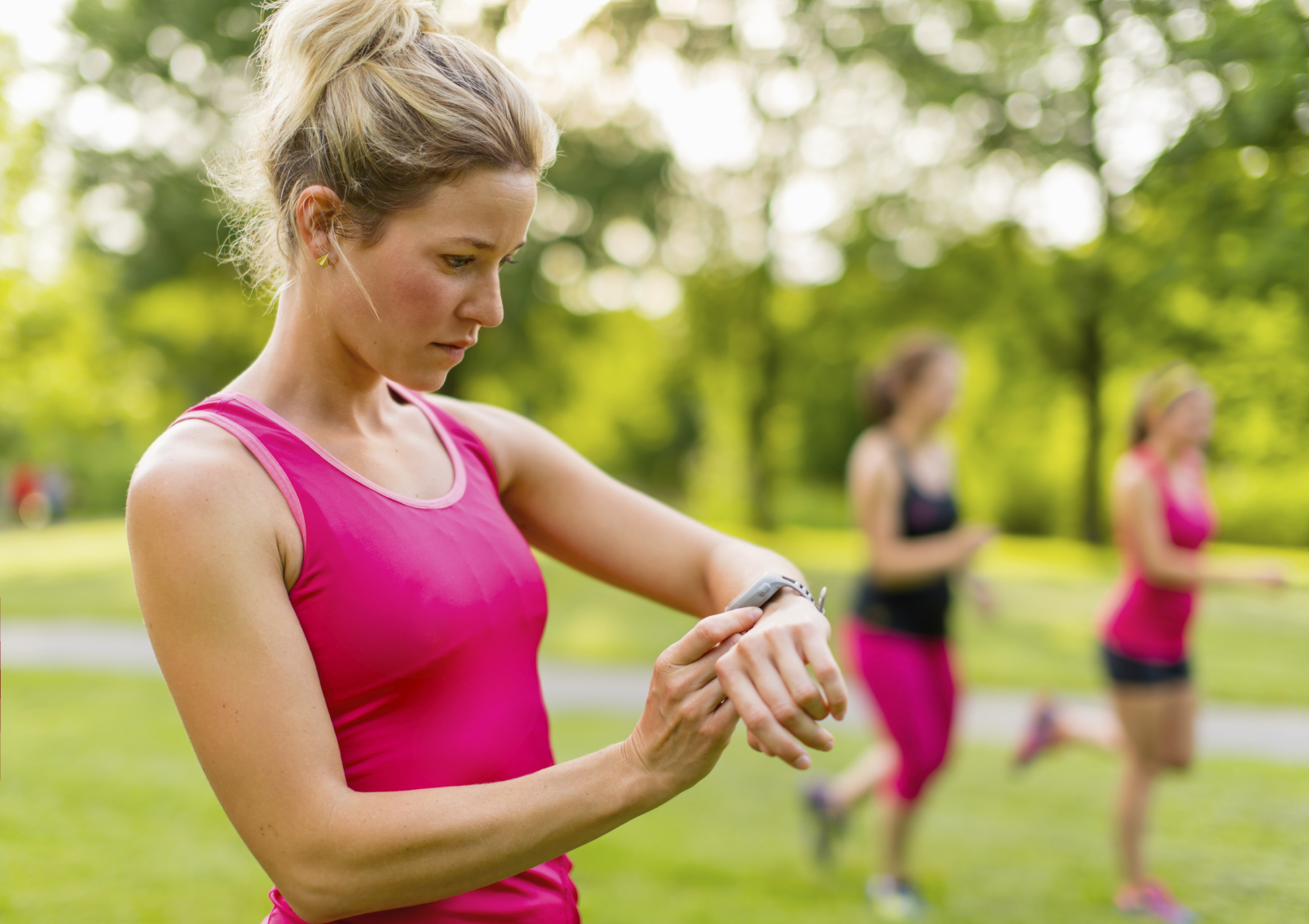 Portrait of an athlete using her watch to mesure her pulse while running with friends