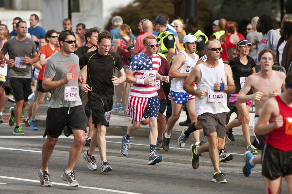 Atlanta, GA, USA - July 4, 2014:  A runner dressed in stars and stripes from head to toe, runs toward the finish line of of the Atlanta Peachtree Road Race on Independence Day.